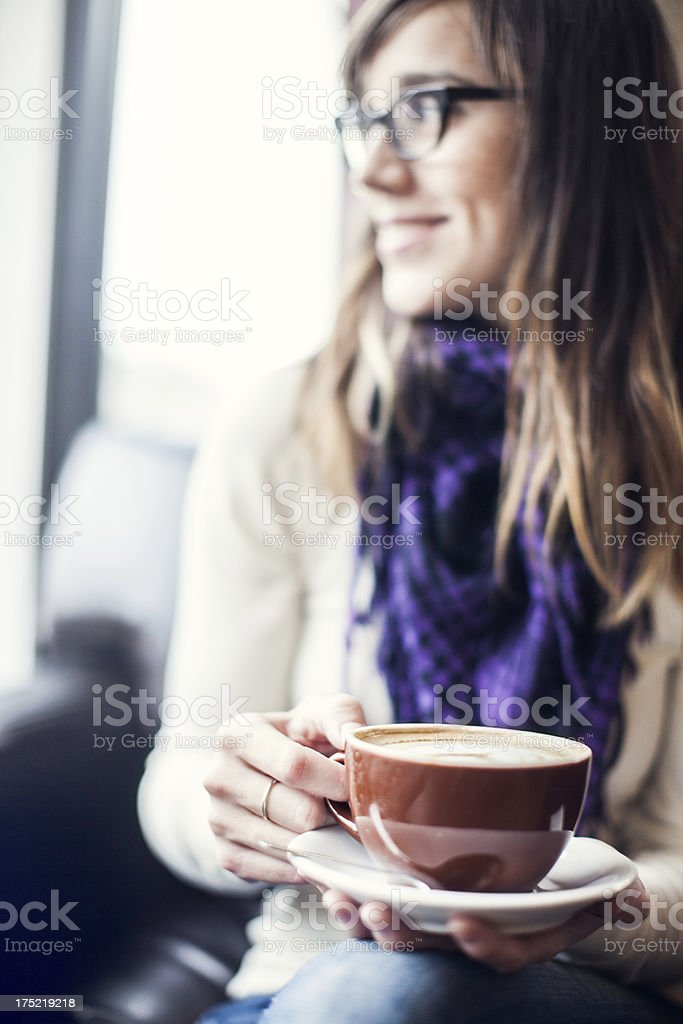Young woman wearing glasses holding coffee cup royalty-free stock photo