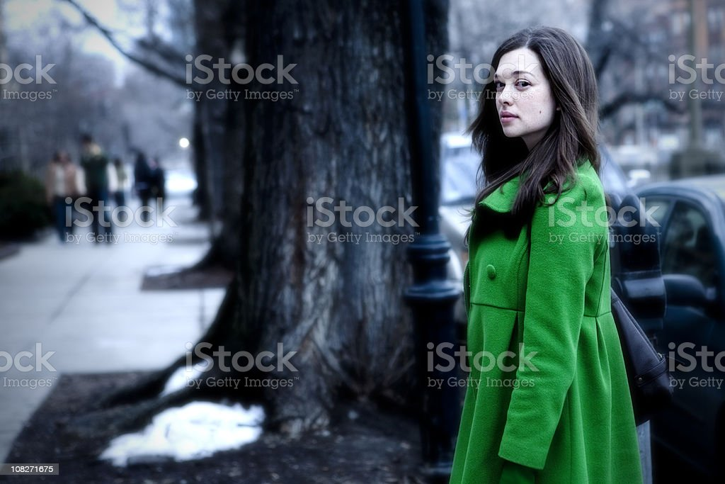 Young Woman Wearing Green Coat on City Street royalty-free stock photo