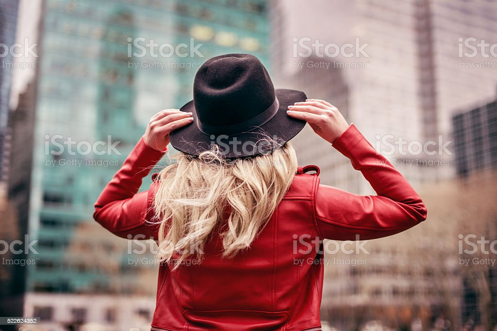 young woman wearing hat walking on streets of New York royalty-free stock photo