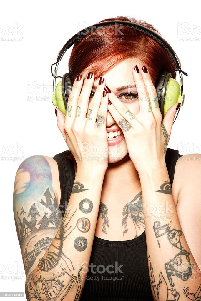 Young Woman Wearing Headphones and Covering Face with Hands royalty-free stock photo