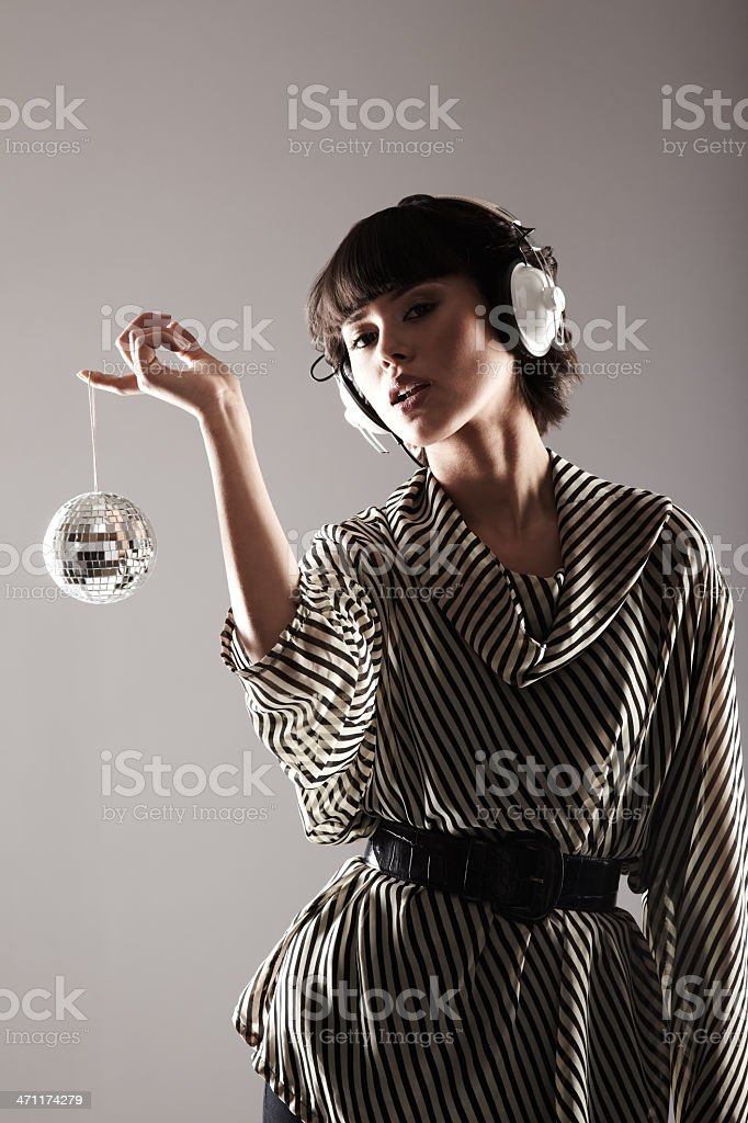 Young woman wearing headphones with disco ball royalty-free stock photo