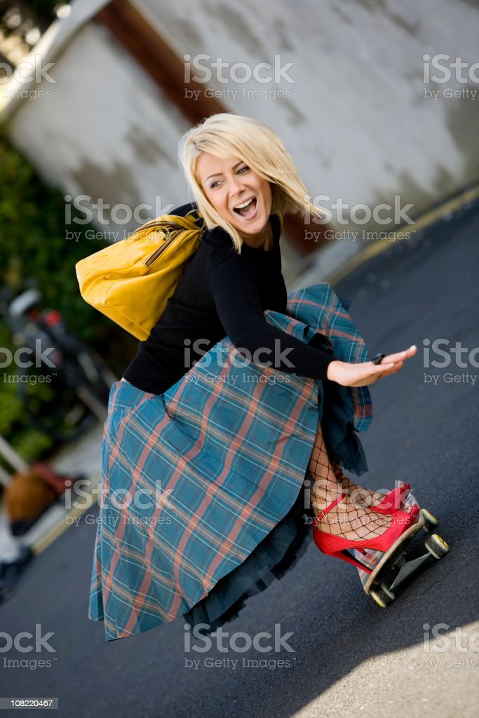 Young Woman Wearing High Heels and Riding Skateboard stock photo