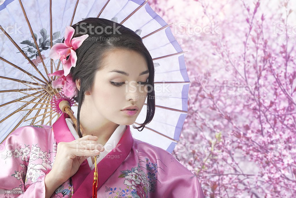 Young  Woman Wearing Kimono Dress with Umbrella in Garden. stock photo