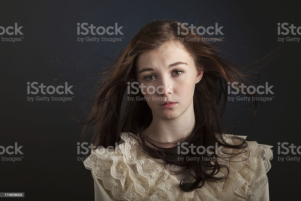 Young Woman Wearing Lace Dress with Hair Blowing stock photo