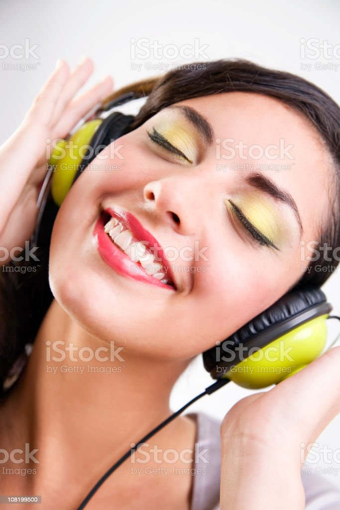 Young Woman Wearing Make-Up and Listening to Headphones royalty-free stock photo