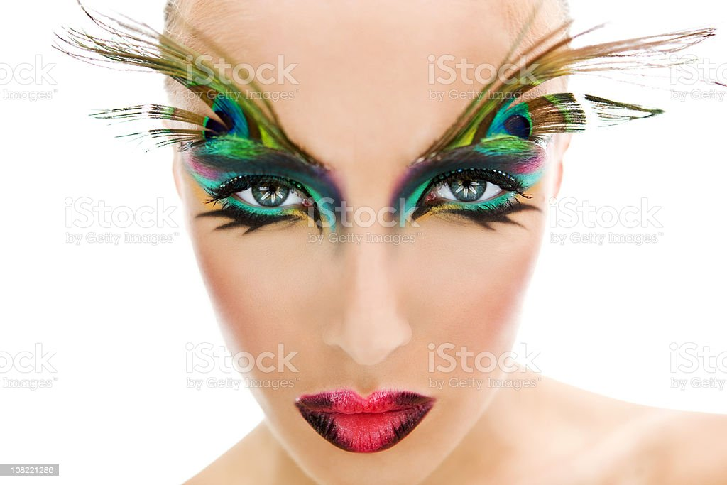 Young Woman Wearing Make-Up and Peacock Feathers on Eyes royalty-free stock photo