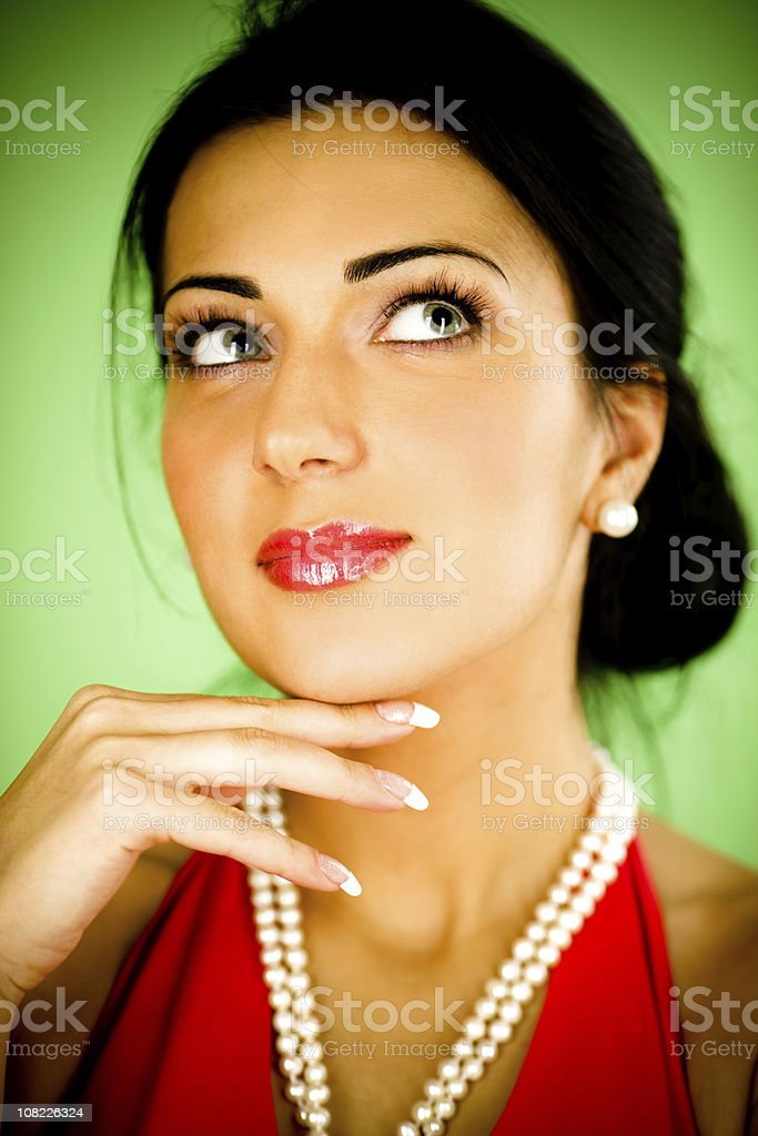 Young Woman Wearing Pearls on Green Background royalty-free stock photo
