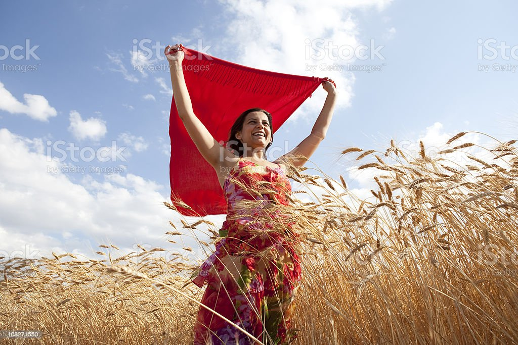 Young Woman Wearing Red Dress Holding Reddish Scarf In Wind royalty-free stock photo