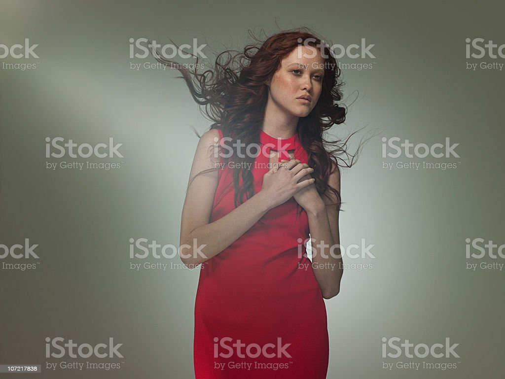 Young woman wearing red dress posing as Aphrodite, portrait stock photo