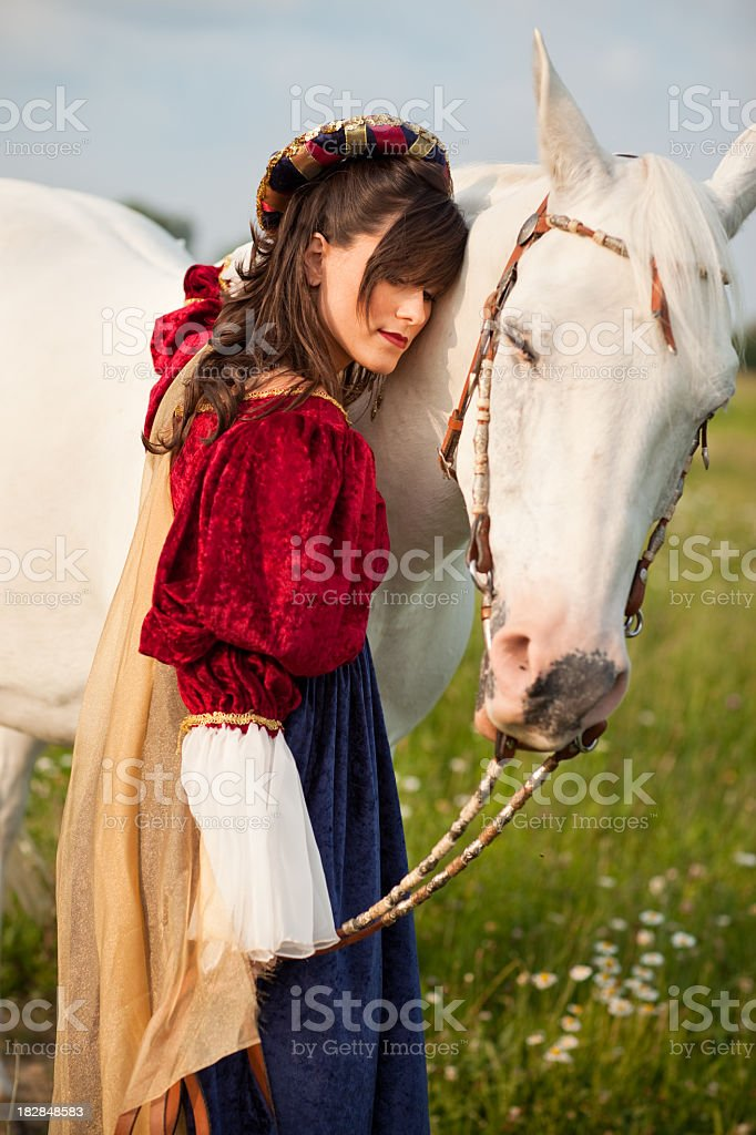 Young Woman Wearing Renaissance Dress Hugging Her Horse stock photo