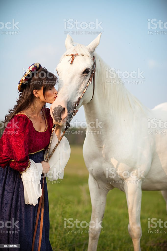 Young Woman Wearing Renaissance Dress Kissing Her Horse stock photo