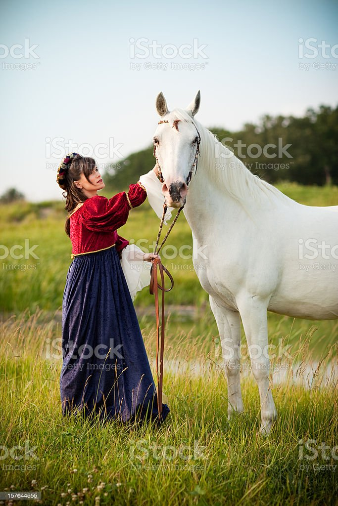 Young Woman Wearing Renaissance Dress Petting Horse in Field stock photo