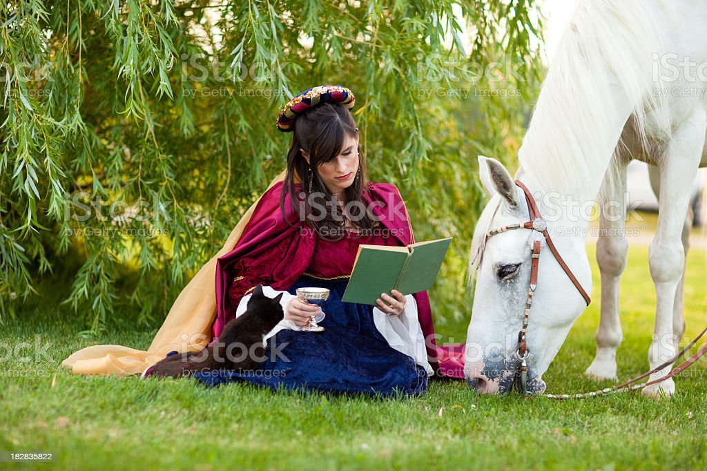 Young Woman Wearing Renaissance Dress Reading Under Tree with Horse royalty-free stock photo