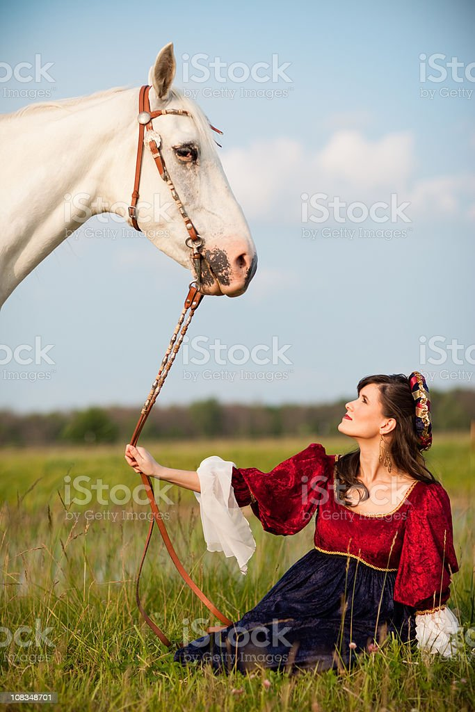 Young Woman Wearing Renaissance Dress Sitting in Field with Horse stock photo