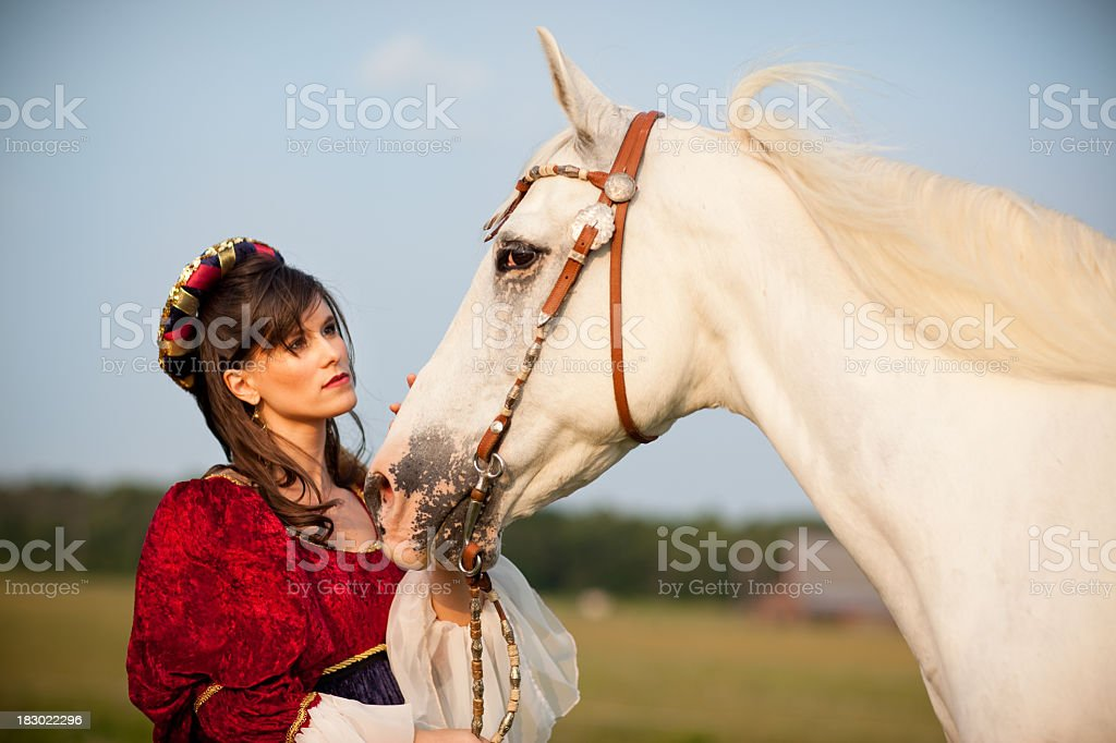 Young Woman Wearing Renaissance Dress while Petting Her Horse royalty-free stock photo