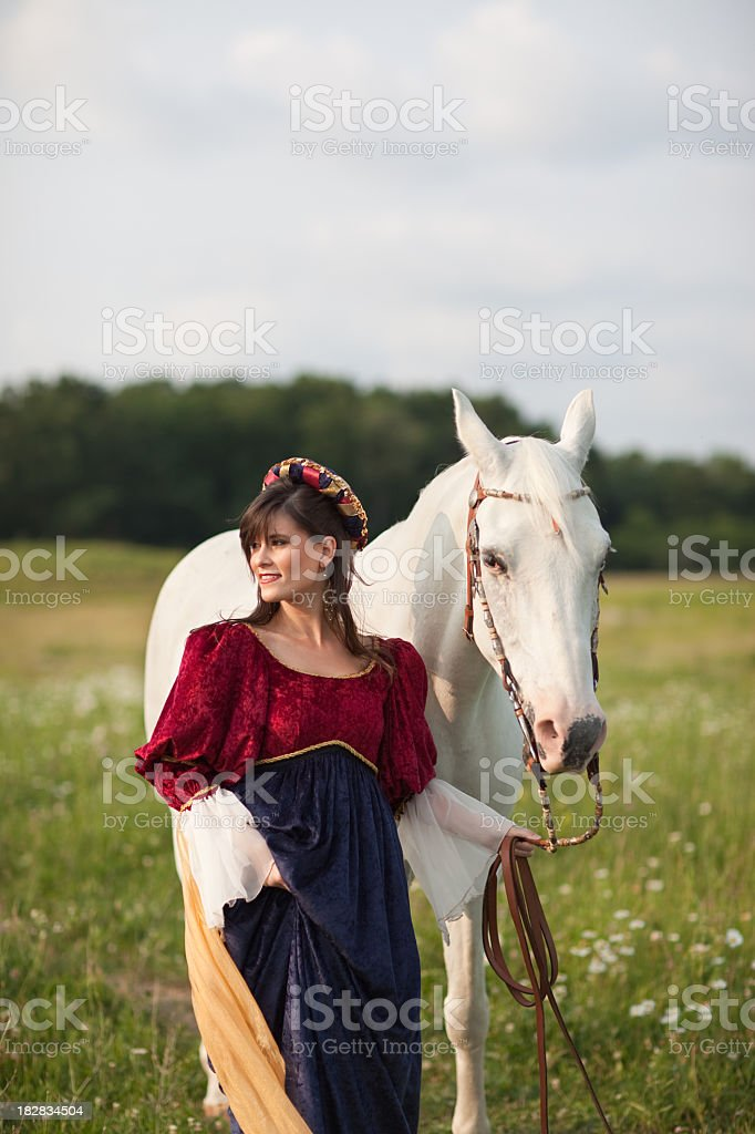 Young Woman Wearing Renaissance Dress with Horse Walking in Field stock photo
