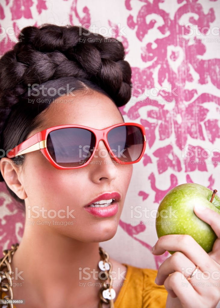 Young Woman Wearing Retro Sunglasses Eating Apple royalty-free stock photo
