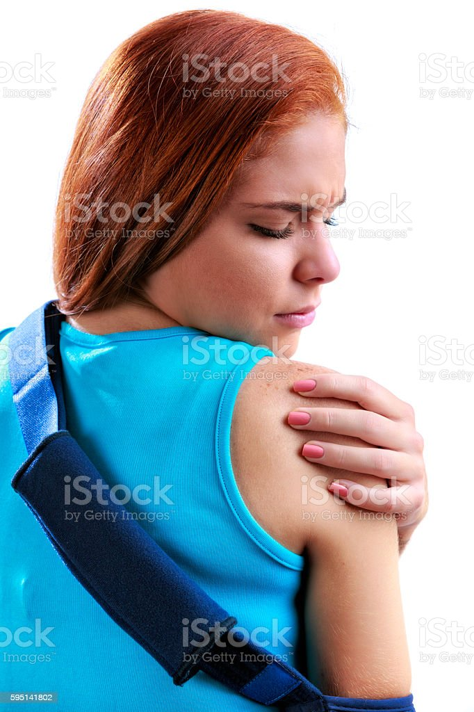 Young woman wearing shoulder brace due to rotator cuff pain stock photo