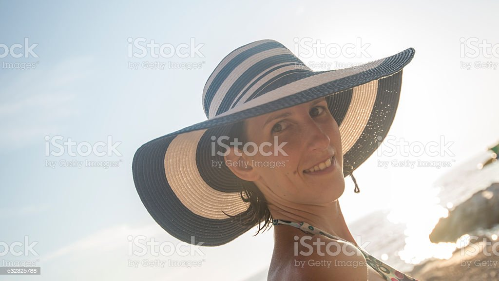 Young woman wearing striped straw hat and swimsuit stock photo