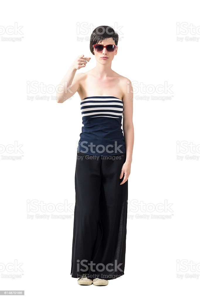 Young woman wearing sunglasses pointing finger at camera stock photo