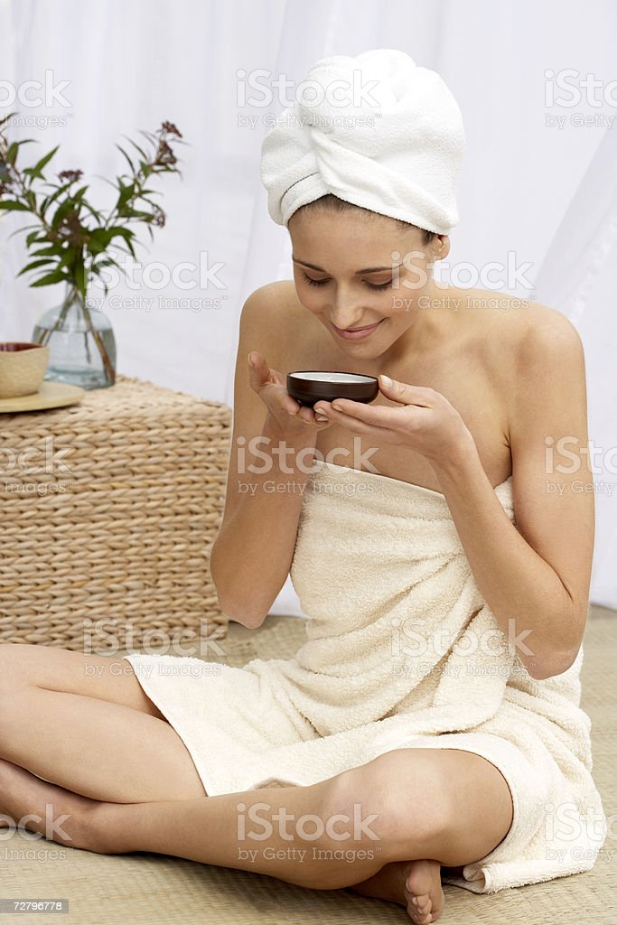 Young woman wearing towel, sitting cross-legged, drinking tea royalty-free stock photo