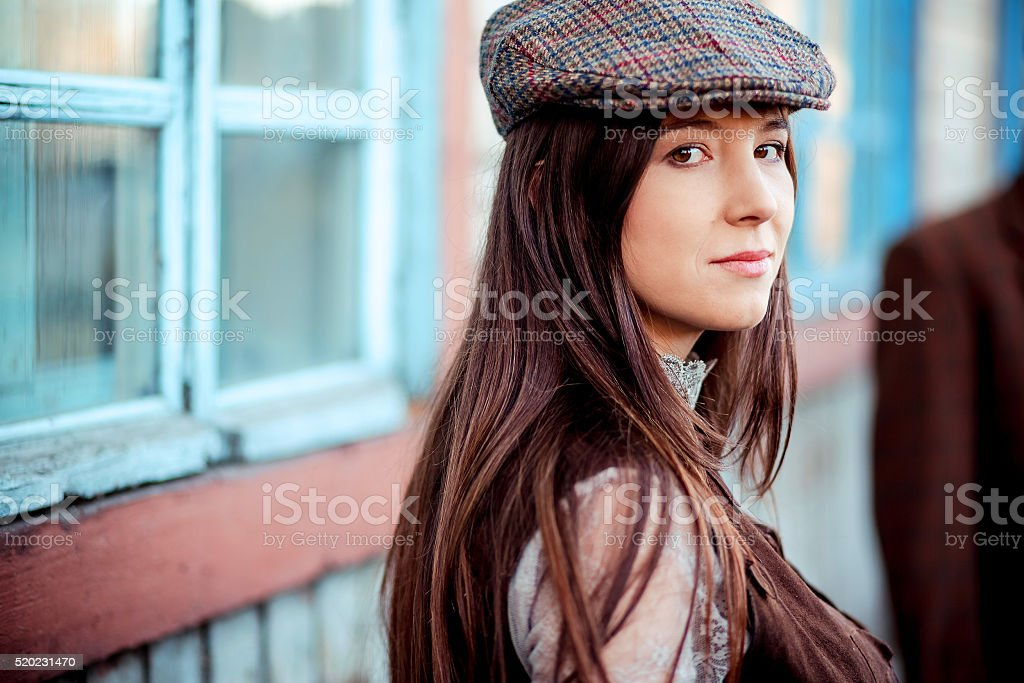 Young woman wearing tweed flat cap old fashioned portrait brown stock photo
