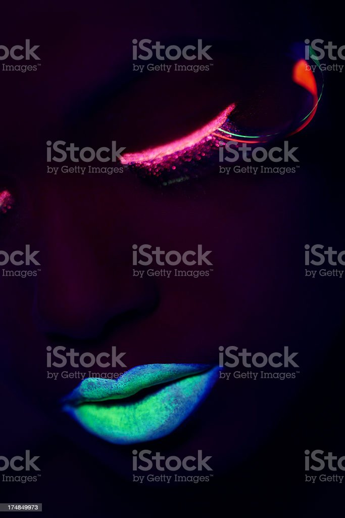 Young woman wearing UV make up against black background stock photo