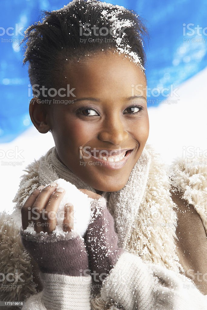 Young Woman Wearing Warm Winter Clothes Holding Snowball royalty-free stock photo