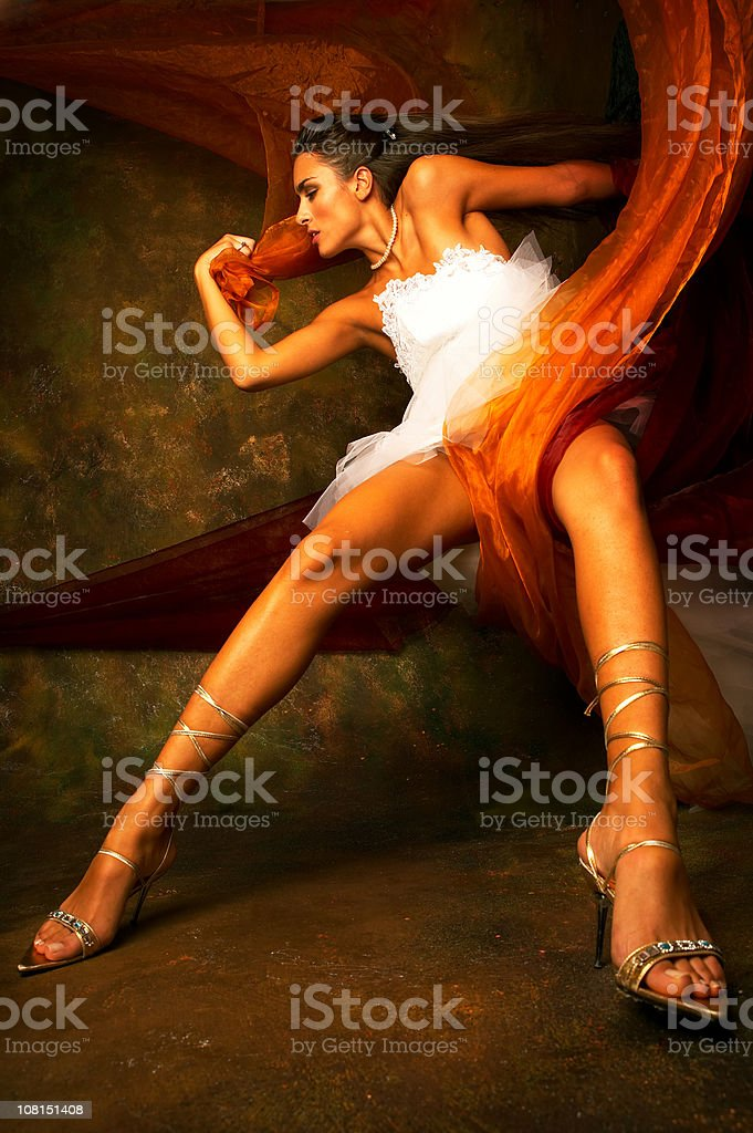 Young Woman Wearing White Dress and Posing with Orange Silk royalty-free stock photo
