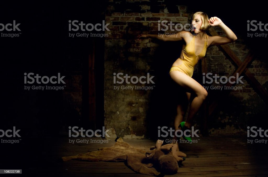 Young Woman Wearing Yellow Bathing Suit Tripping Over Moose Doll royalty-free stock photo