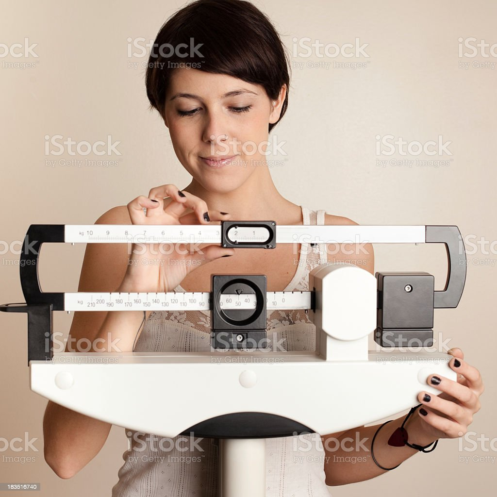 Young woman weighing herself on scale royalty-free stock photo