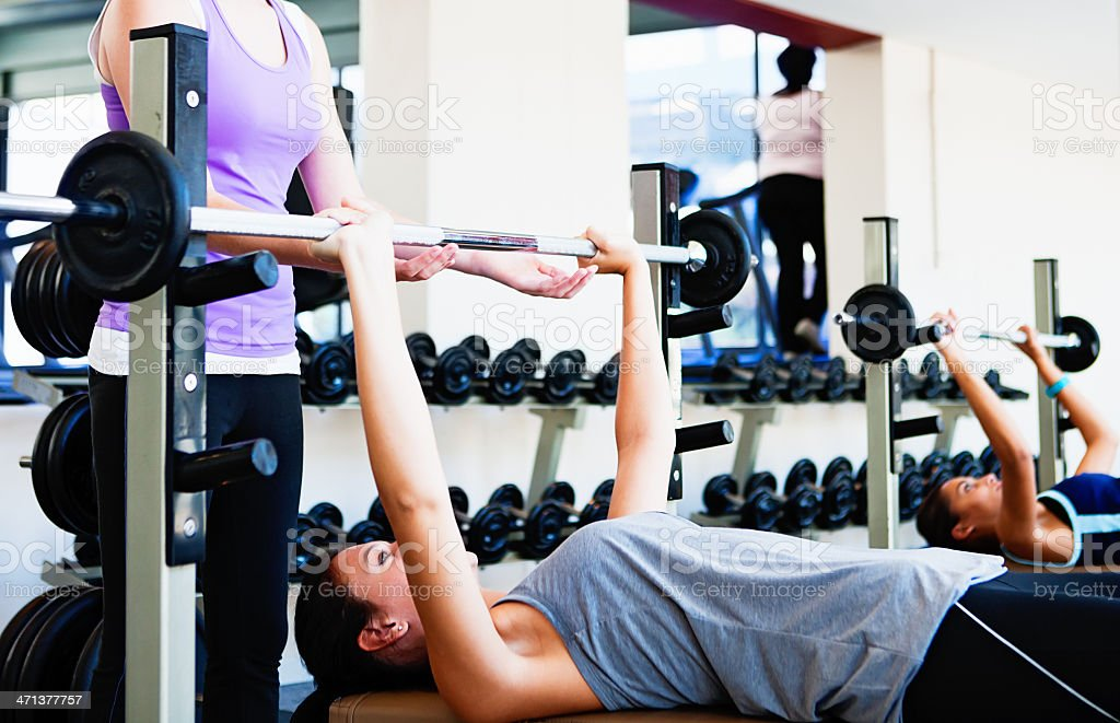 Young woman weightlifting as friend spots for her stock photo