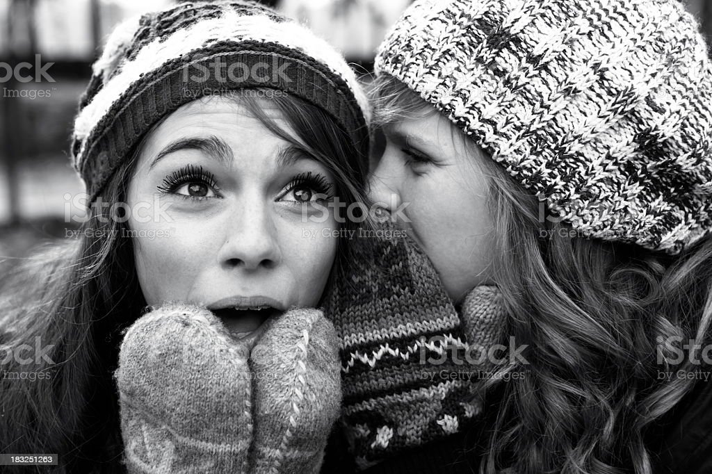 Young woman whispering into ear of woman in winter clothing stock photo