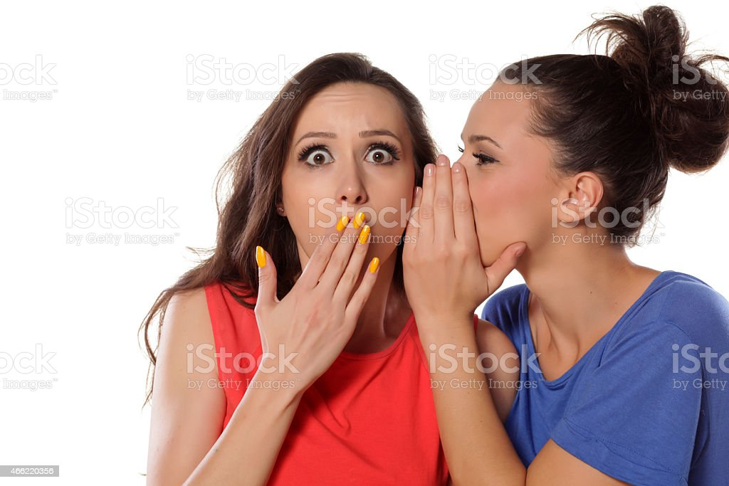 Young woman whispers to her mate shocking news stock photo