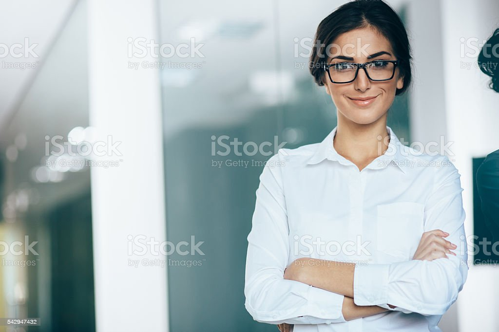Portrait of young woman wearing white shirt and glasses, with arms...