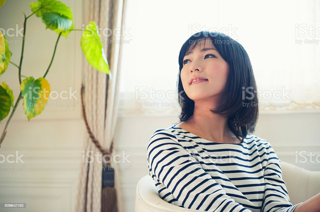 Young woman who sits down on a chair stock photo