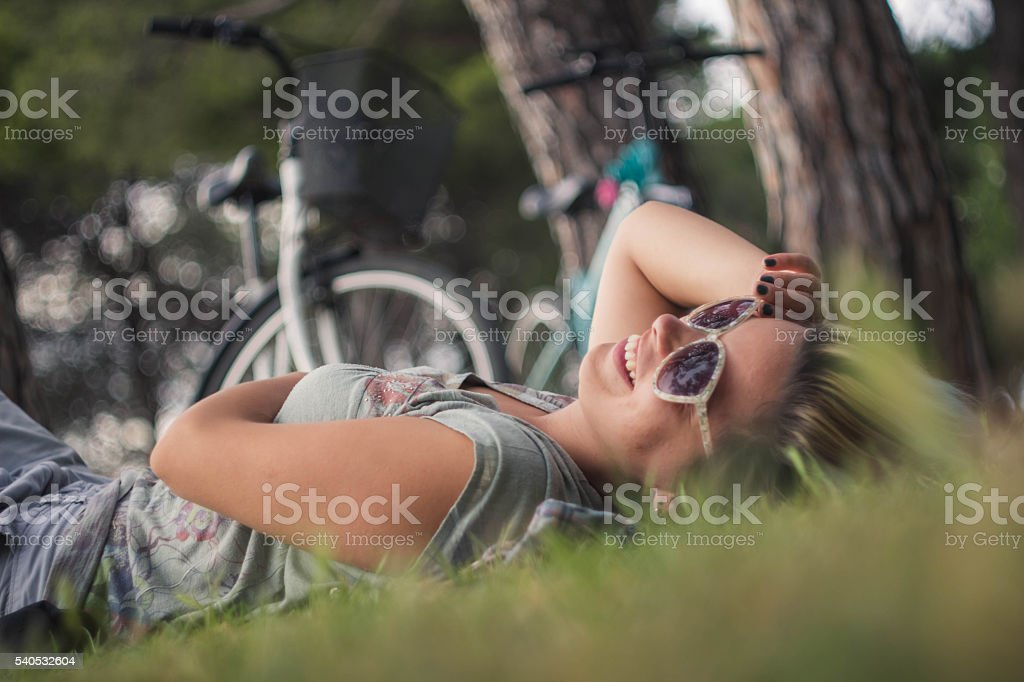 young woman with a bike lying on the grass stock photo