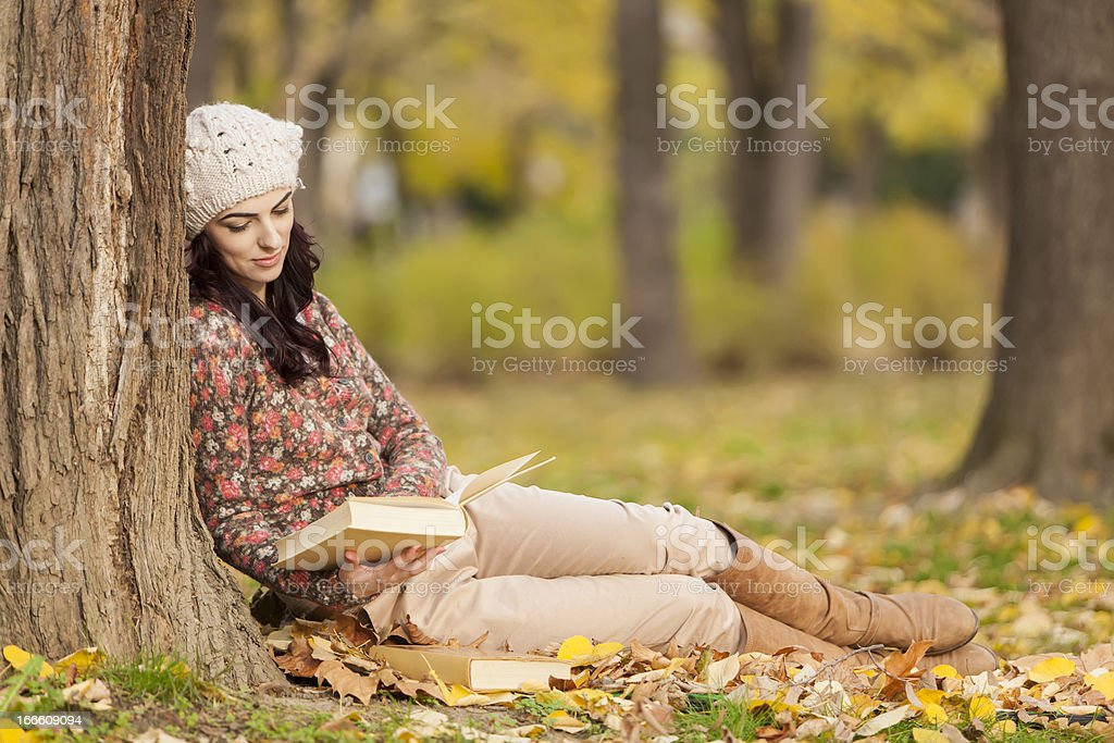 Young woman with a book in the forest royalty-free stock photo