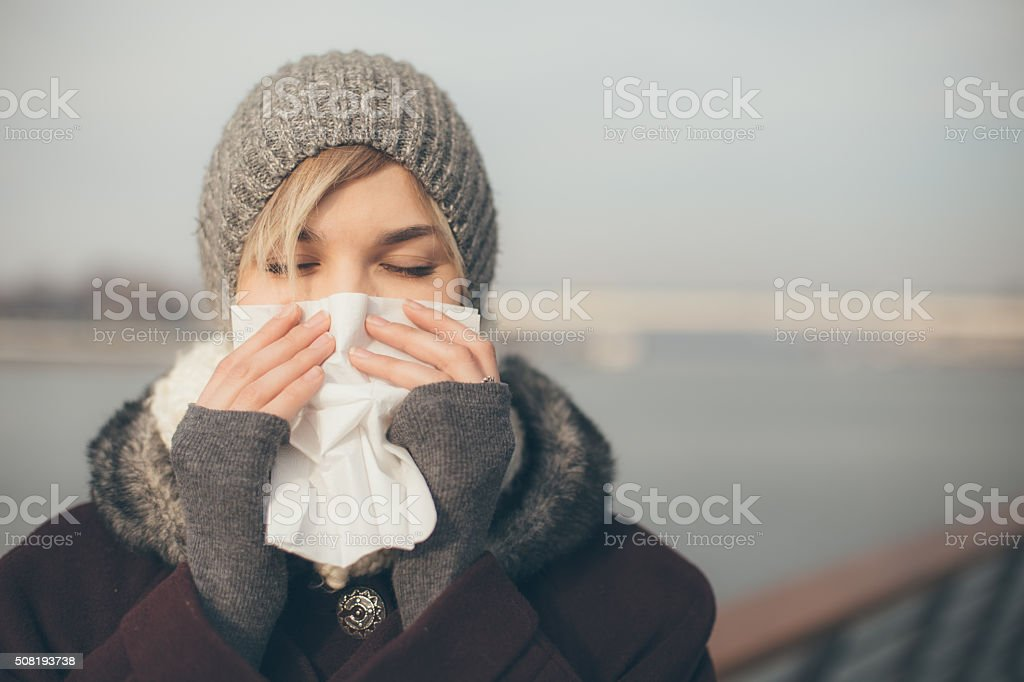 Young woman with a cold holding a tissue stock photo