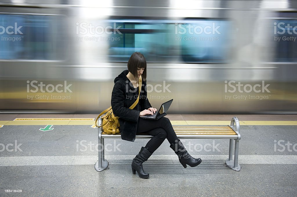 Young woman with a computer in the subway station stock photo