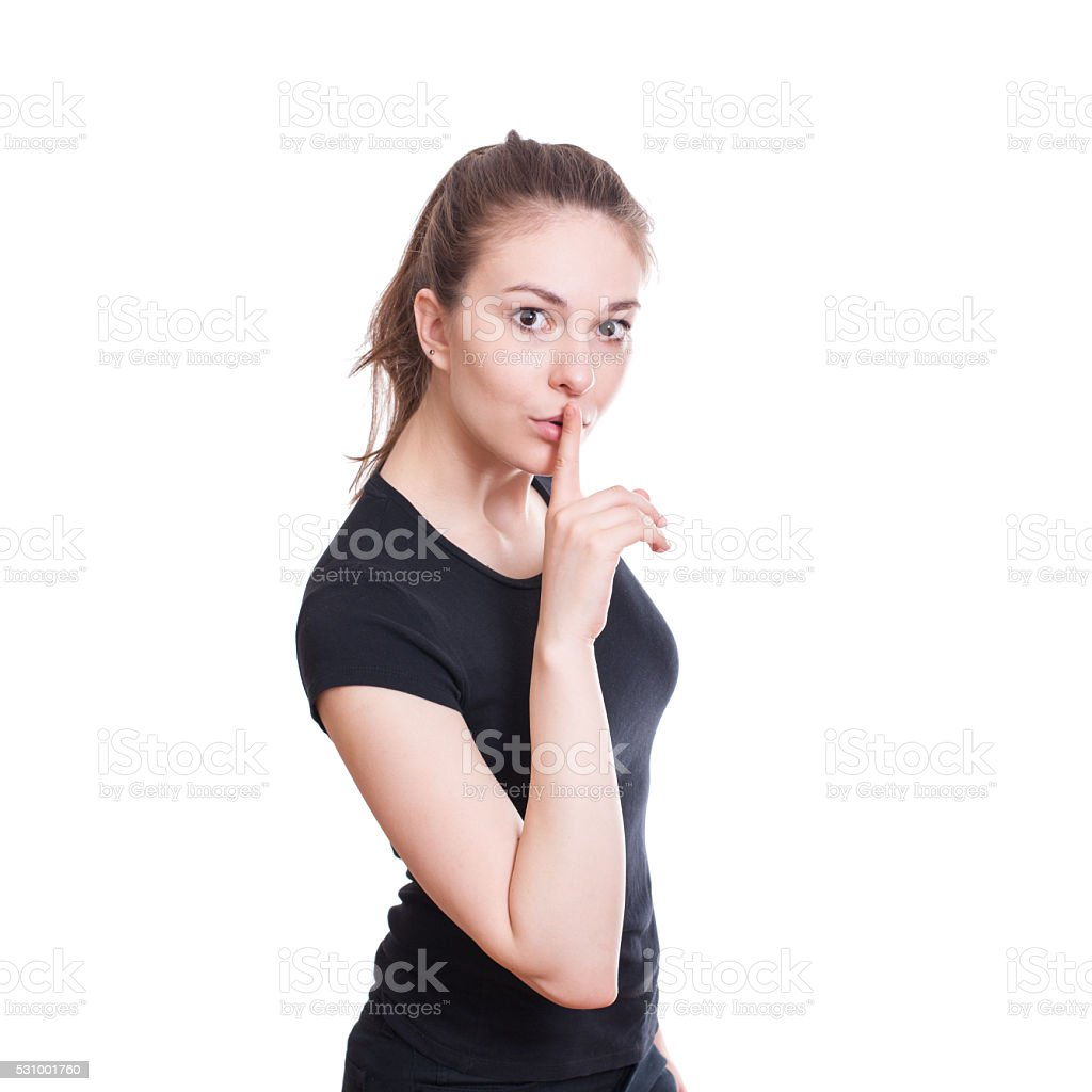 Young woman with a finger near her lips. stock photo