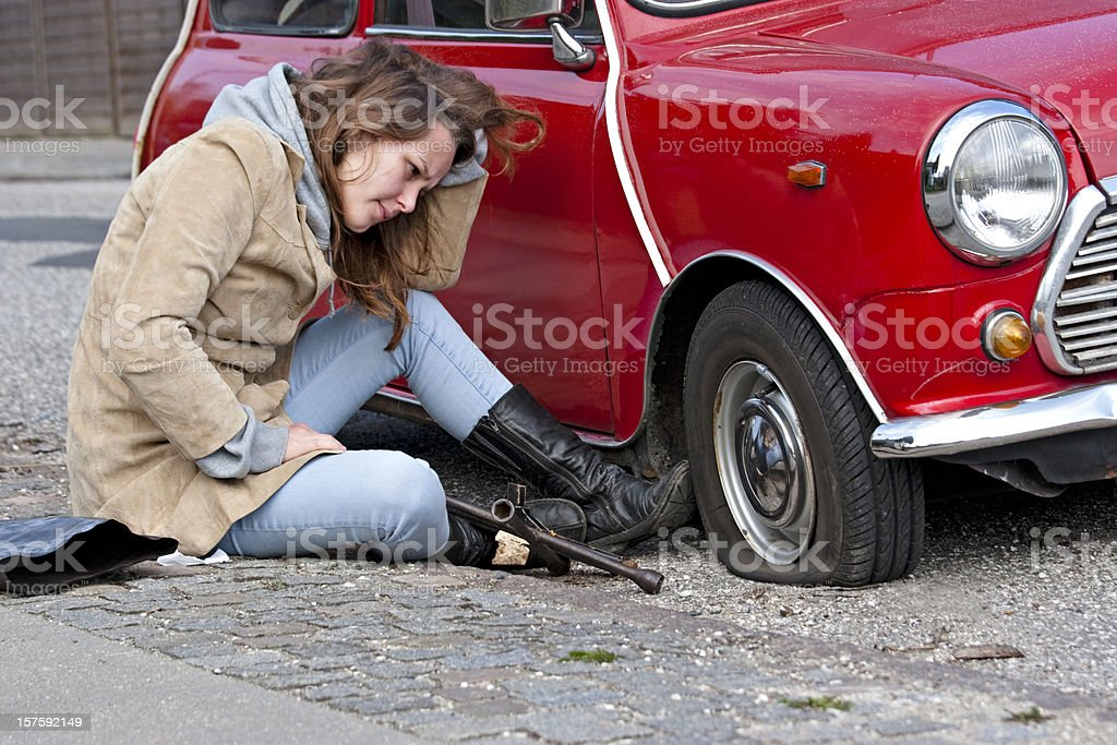 Young woman with a flat tire royalty-free stock photo