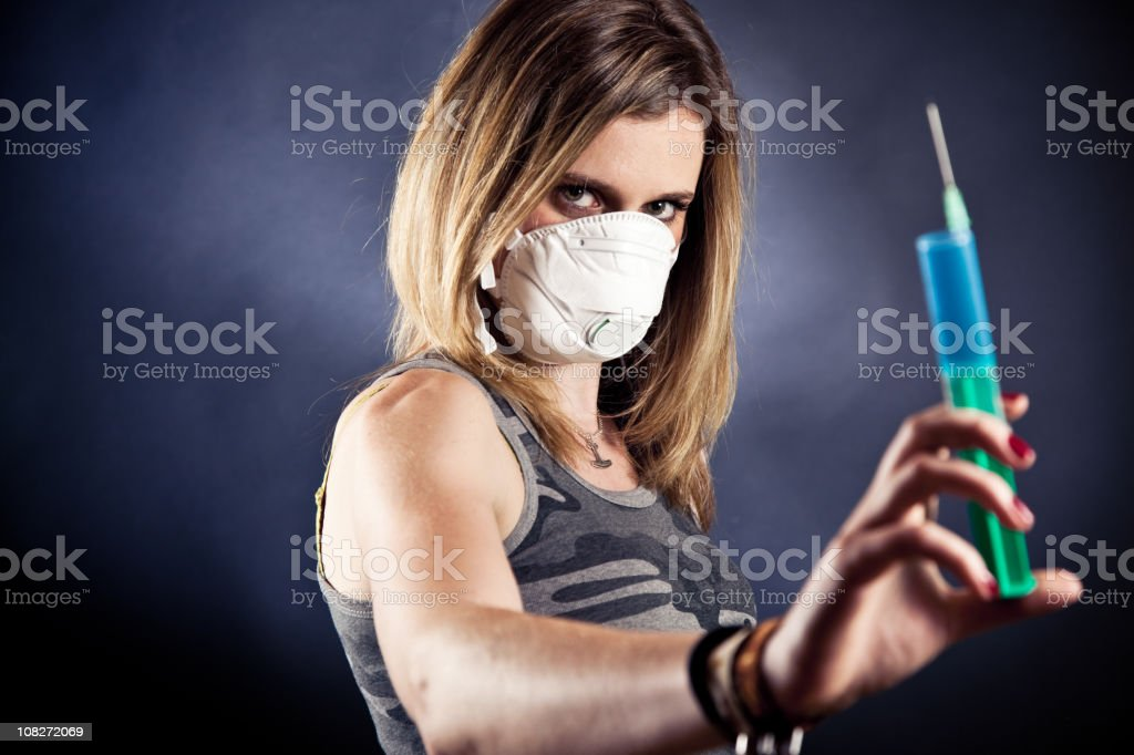 young woman with a flu mask, holding the cure royalty-free stock photo