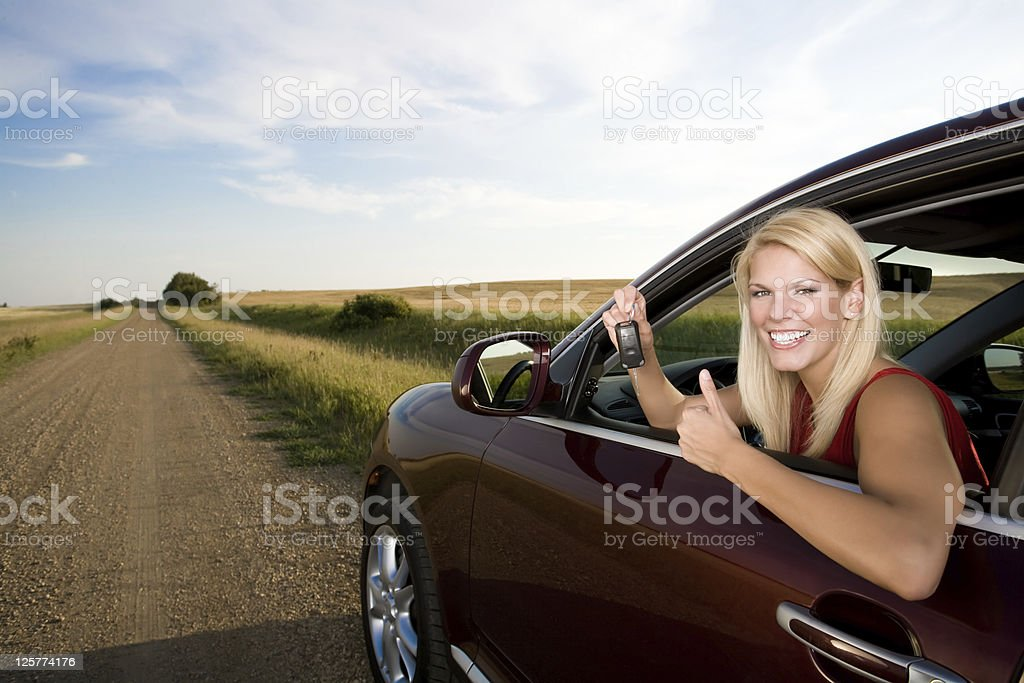 Young woman with a key to her new car royalty-free stock photo