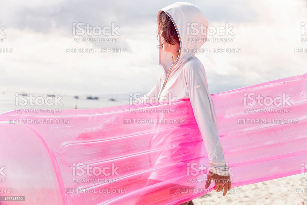 Young Woman with a Pink Float at the Beach royalty-free stock photo