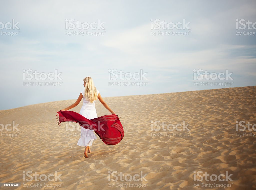 Young woman with a red scarf walking in the desert royalty-free stock photo