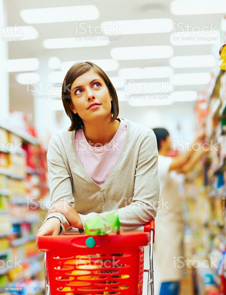 Young woman with a red shopping cart at supermarket royalty-free stock photo