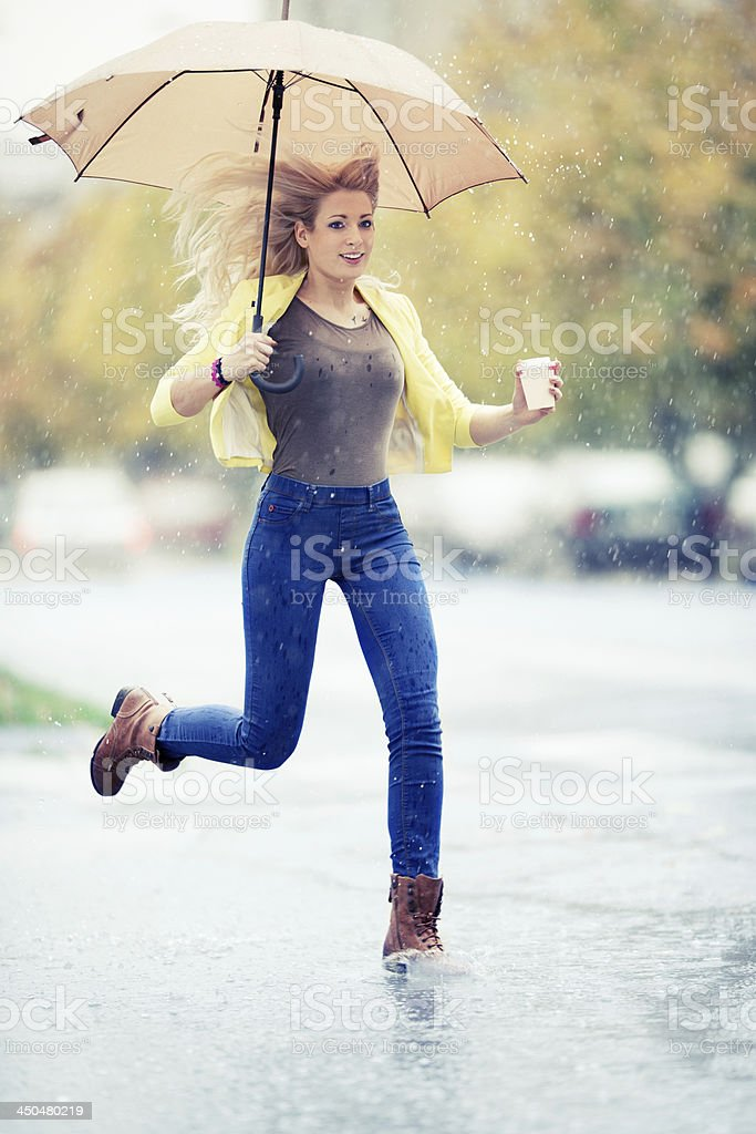 Young woman with a take-away coffee under the rain royalty-free stock photo