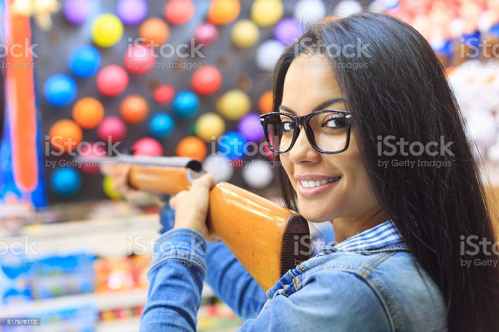 Young woman with air gun for pop a ballon game stock photo