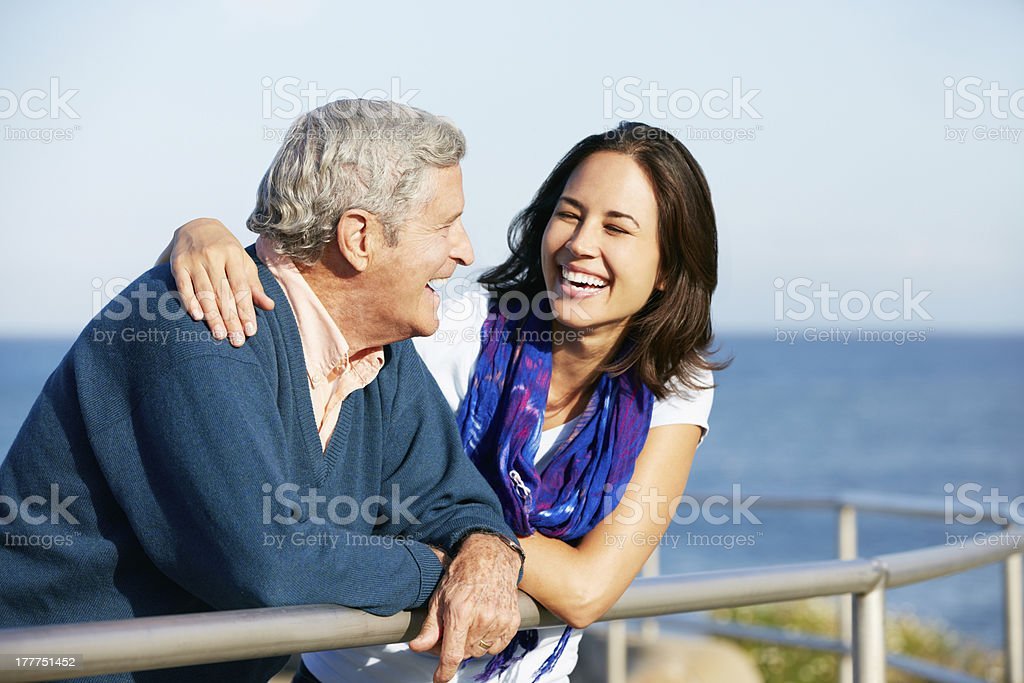 Young woman with arm around father near the sea stock photo